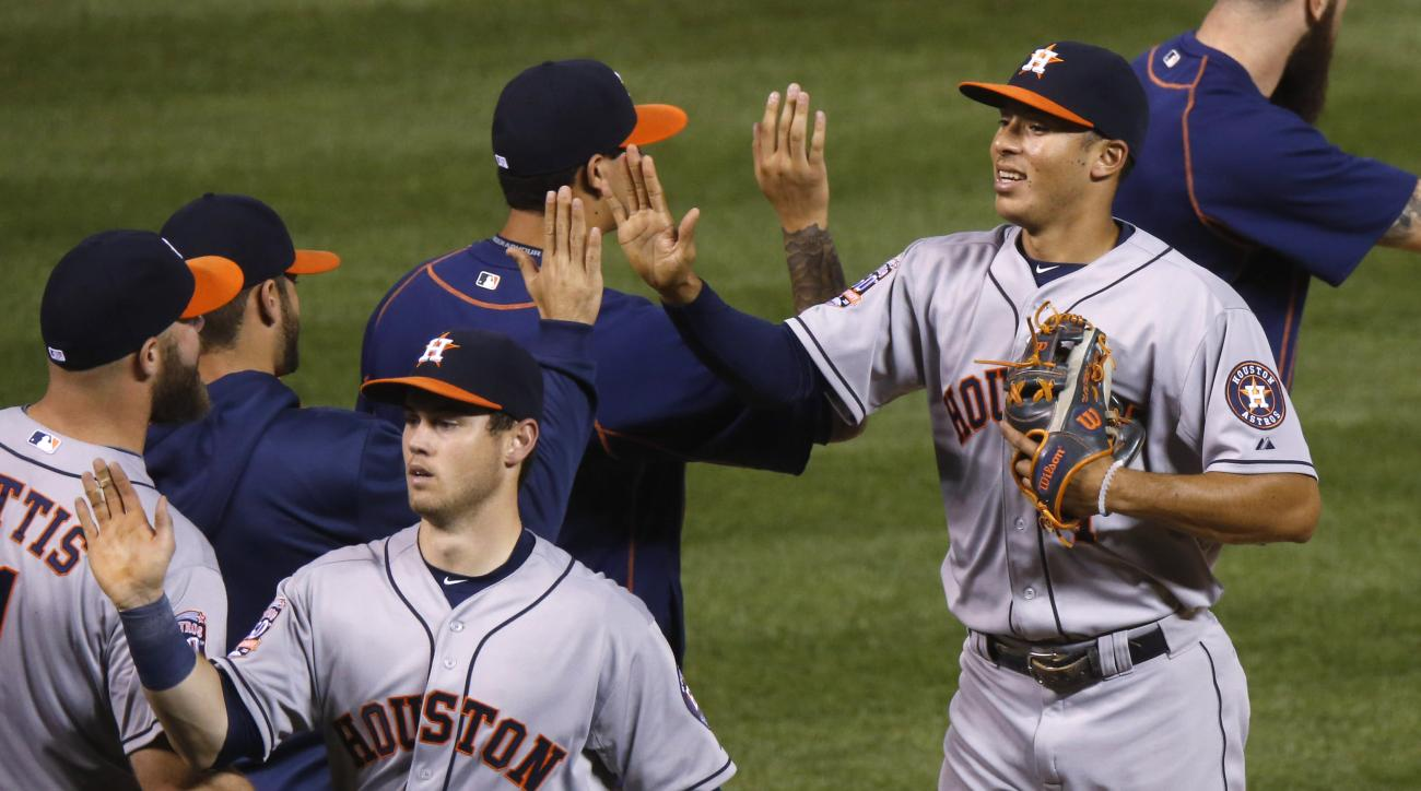 Houston Astros shortstop Carlos Correa, front right, and left fielder Preston Tucker, front left, are congratulated by teammates after retiring the Colorado Rockies in the ninth inning of a baseball game Wednesday, June 17, 2015, in Denver. Houston won 8-
