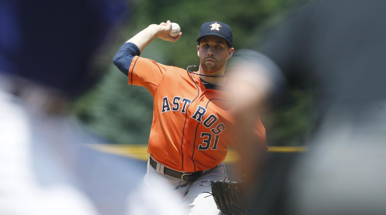 Houston Astros starting pitcher Collin McHugh, center, is framed between Colorado Rockies' Nolan Arenado, front left, and home plate umpire David Rackley as McHugh delivers a pitch in the first inning of an interleague baseball game Thursday, June 18, 201