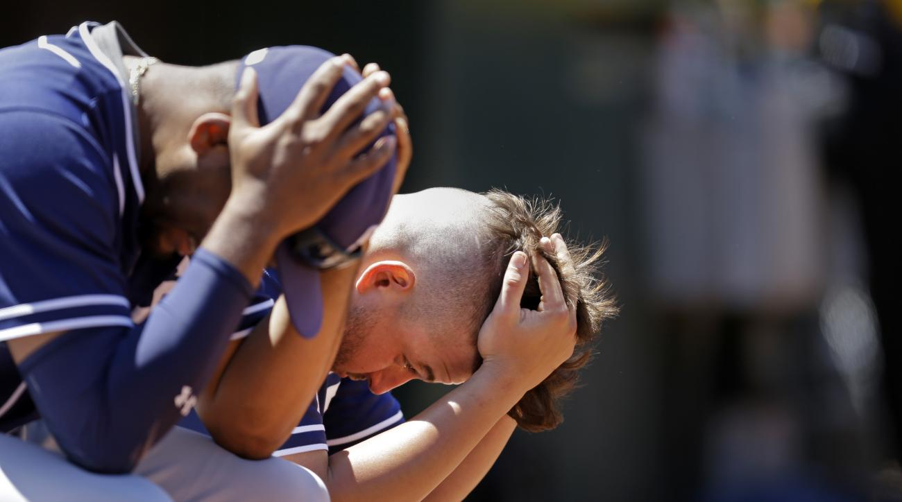 San Diego Padres' Odrisamer Despaigne, left, and Yonder Alonso hold their heads in the dugout during a baseball game against the Oakland Athletics, Thursday, June 18, 2015, in Oakland, Calif. (AP Photo/Ben Margot)