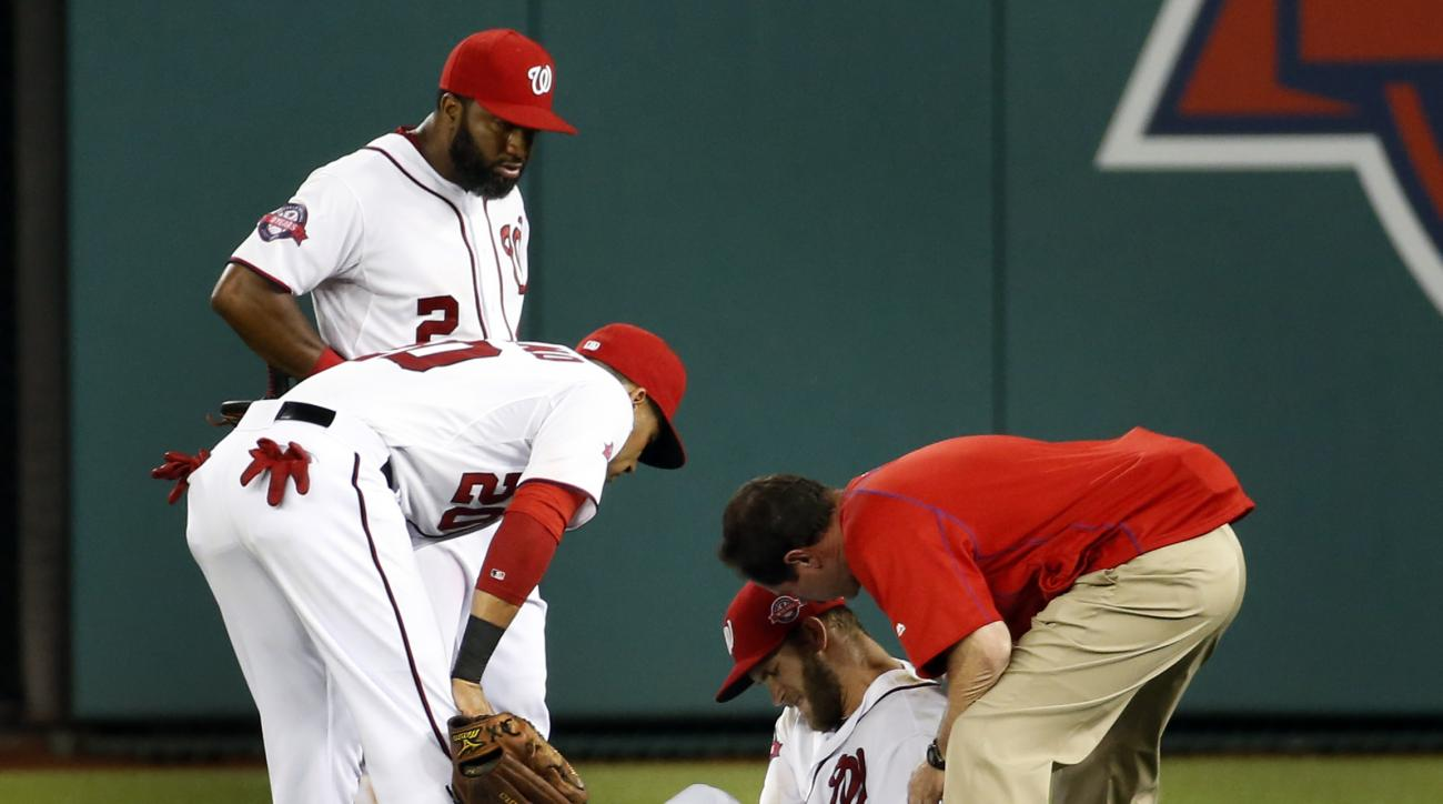 Washington Nationals' Ian Desmond (20) and center fielder Denard Span (2) look at right fielder Bryce Harper as he holds his left leg after an injury, as head athletic trainer Lee Kuntz, right, attends to Harper during the sixth inning of a baseball game