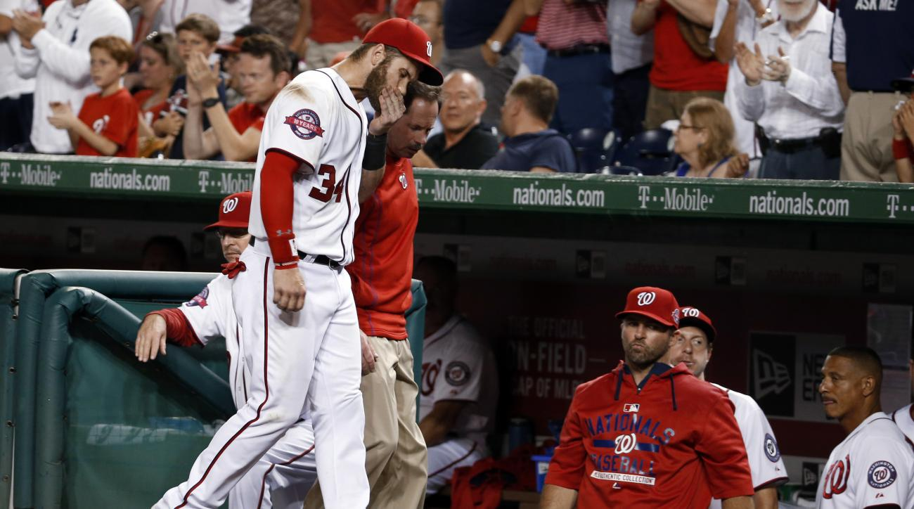 Washington Nationals right fielder Bryce Harper (34) leaves the field with head athletic trainer Lee Kuntz, rear, during the sixth  inning of a baseball game against the Tampa Bay Rays at Nationals Park, Thursday, June 18, 2015, in Washington. (AP Photo/A