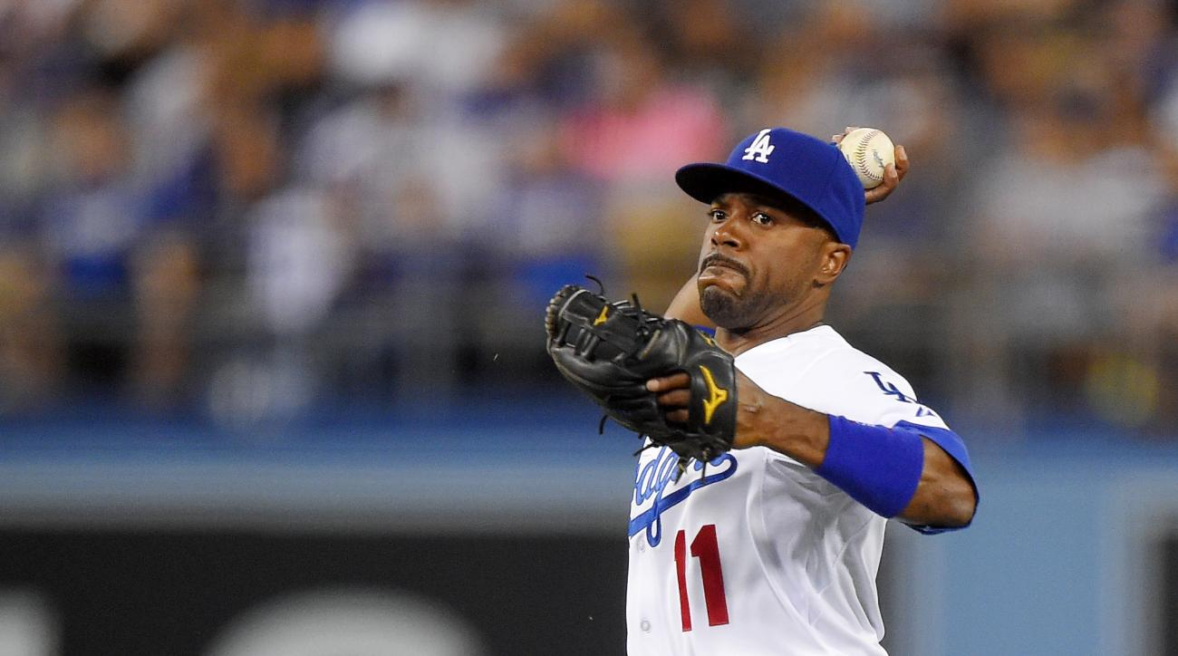 Los Angeles Dodgers shortstop Jimmy Rollins, right, throws out Texas Rangers' Joey Gallo at first as Howie Kendrick ducks during the sixth inning of a baseball game, Thursday, June 18, 2015, in Los Angeles. (AP Photo/Mark J. Terrill)