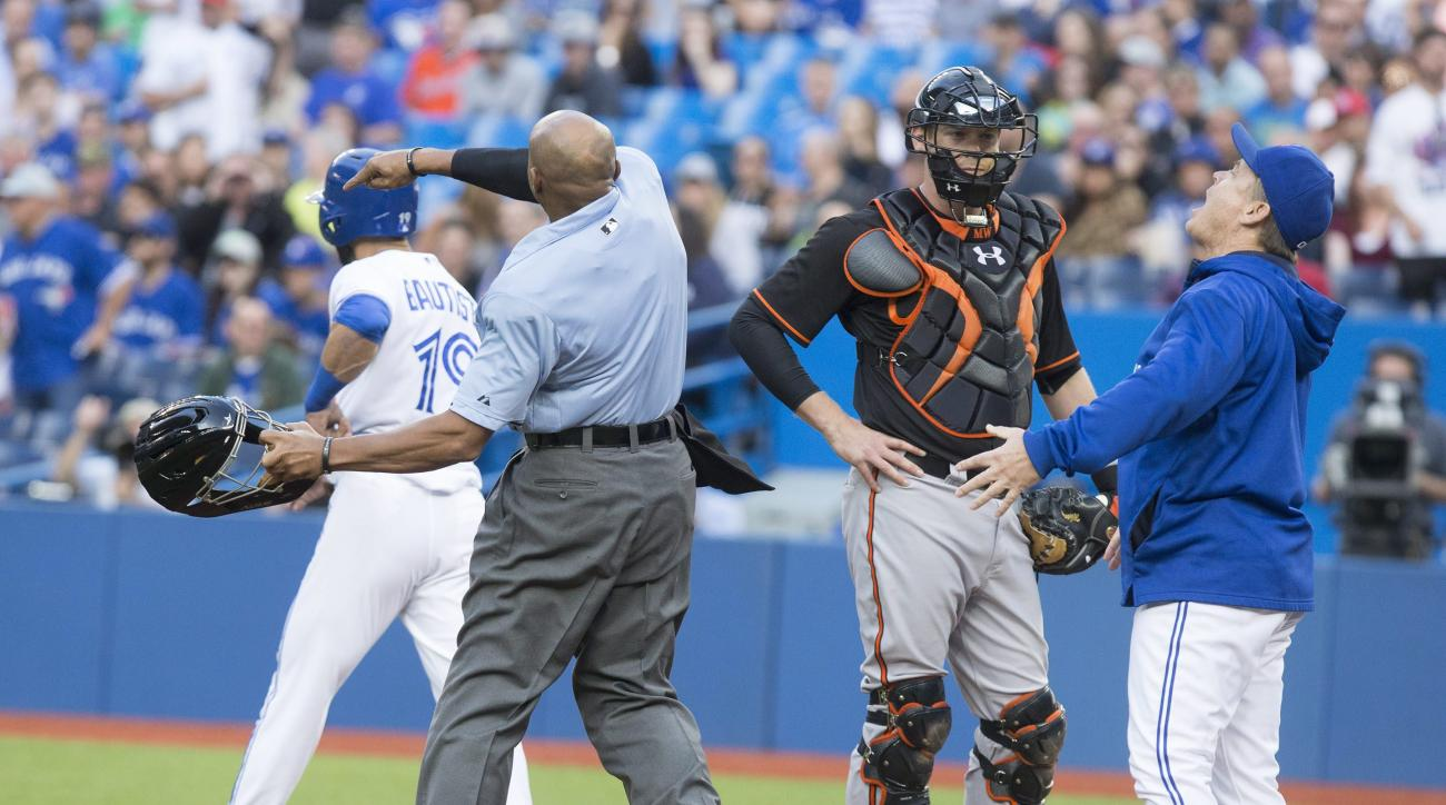 Toronto Blue Jays manager John Gibbons, right, is tossed from a baseball game by home plate umpire CB Bucknor, second from left, as Baltimore Orioles catcher Matt Wieters, second from right, looks on during first-inning action in Toronto, Friday June 19,