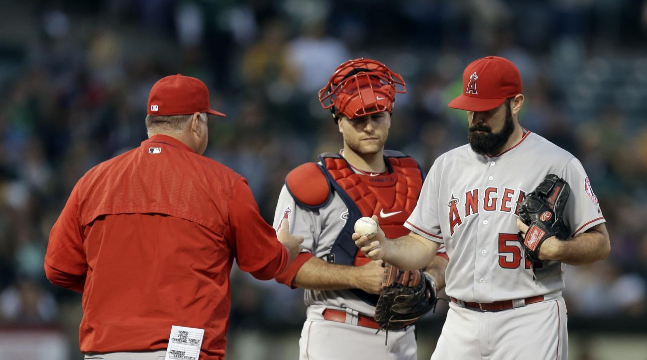 Los Angeles Angels pitcher Matt Shoemaker, right, hands the ball to manager Mike Scioscia after being removed in the fifth inning of a baseball game against the Oakland Athletics Friday, June 19, 2015, in Oakland, Calif. (AP Photo/Ben Margot)