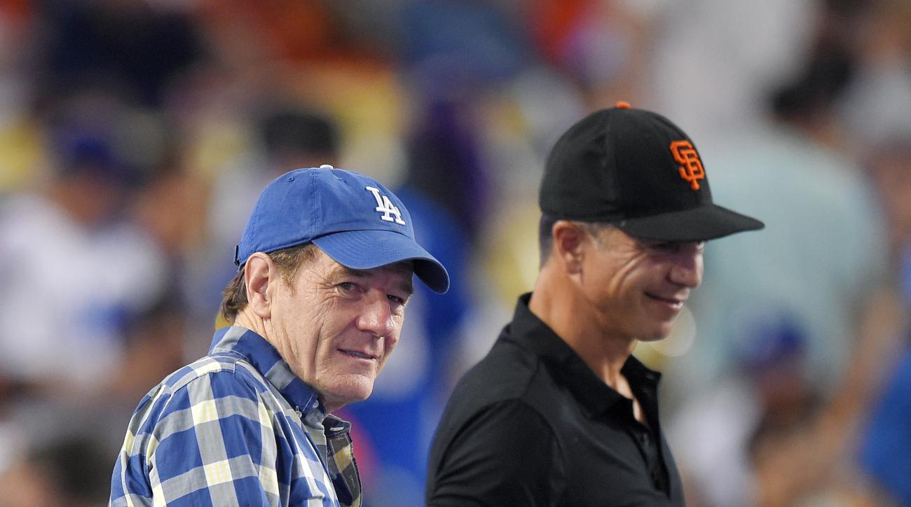 Actor Bryan Cranston, left, watches the Los Angeles Dodgers play the San Francisco Giants at a baseball game, Friday, June 19, 2015, in Los Angeles. (AP Photo/Mark J. Terrill)