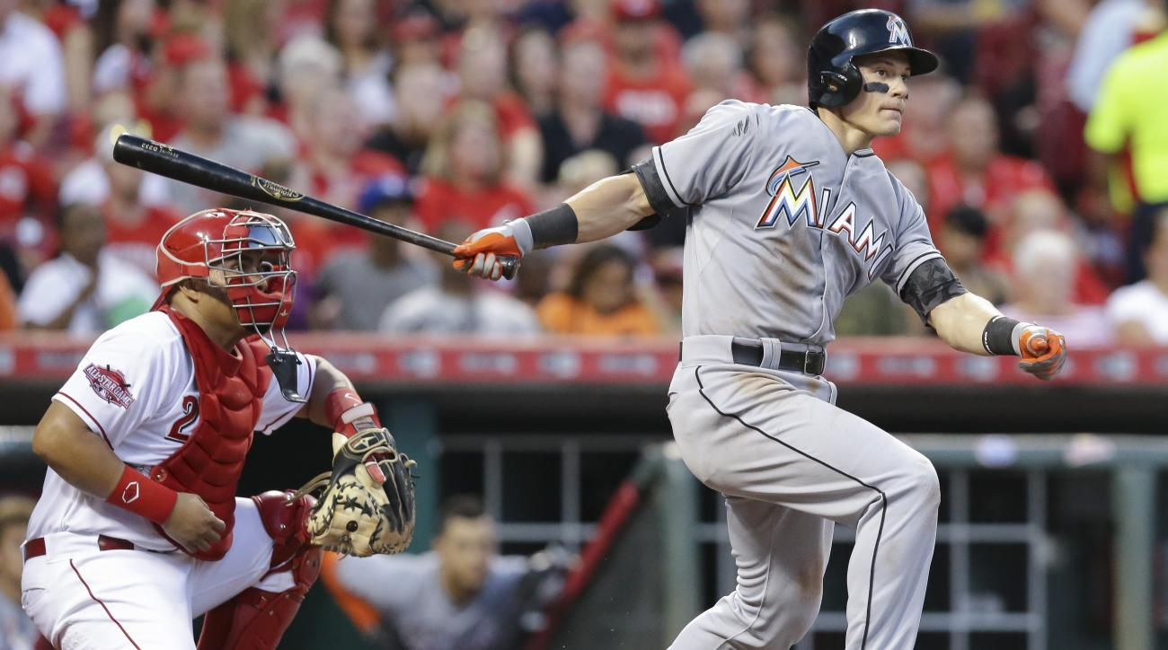 Miami Marlins' Derek Dietrich, right, hits a two-run home run off Cincinnati Reds relief pitcher Manny Parra in the seventh inning of a baseball game, Saturday, June 20, 2015, in Cincinnati. (AP Photo/John Minchillo)