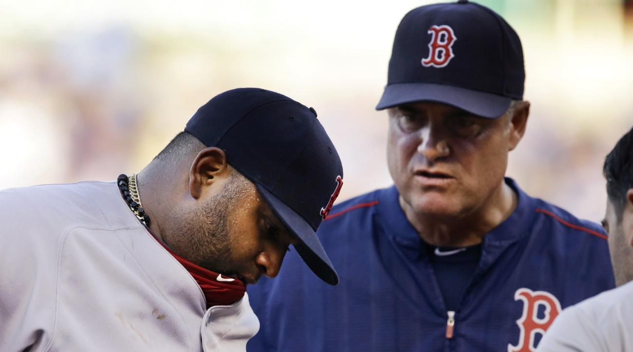 Boston Red Sox third baseman Pablo Sandoval, left, is checked out by a trainer, right, and manager John Farrell, middle, during the fifth inning of a baseball game against the Kansas City Royals at Kauffman Stadium in Kansas City, Mo., Saturday, June 20,