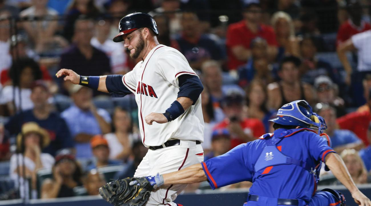Atlanta Braves A.J. Pierzynski, left, scores past  New York Mets catcher Travis d'Arnaud on a Pedro Ciriaco base hit in the sixth inning inning of a baseball game Saturday, June 20, 2015, in Atlanta.  d'Arnaud  was shaken up up the play and left the game.