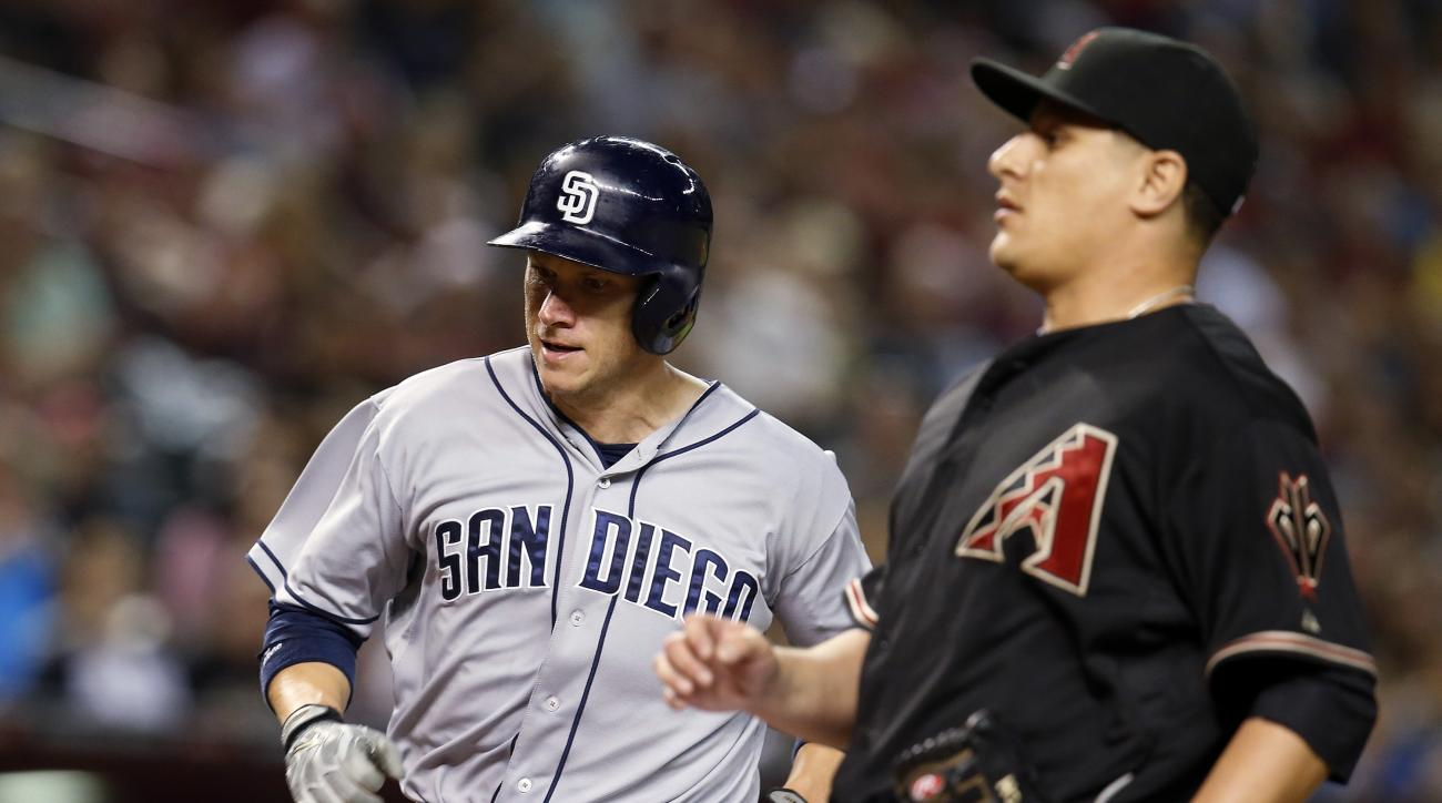 San Diego Padres' Clint Barmes, left, scores on a wild pitch by Arizona Diamondbacks' David Hernandez, right, during the sixth inning of a baseball game, Saturday, June 20, 2015, in Phoenix. (AP Photo/Rick Scuteri)
