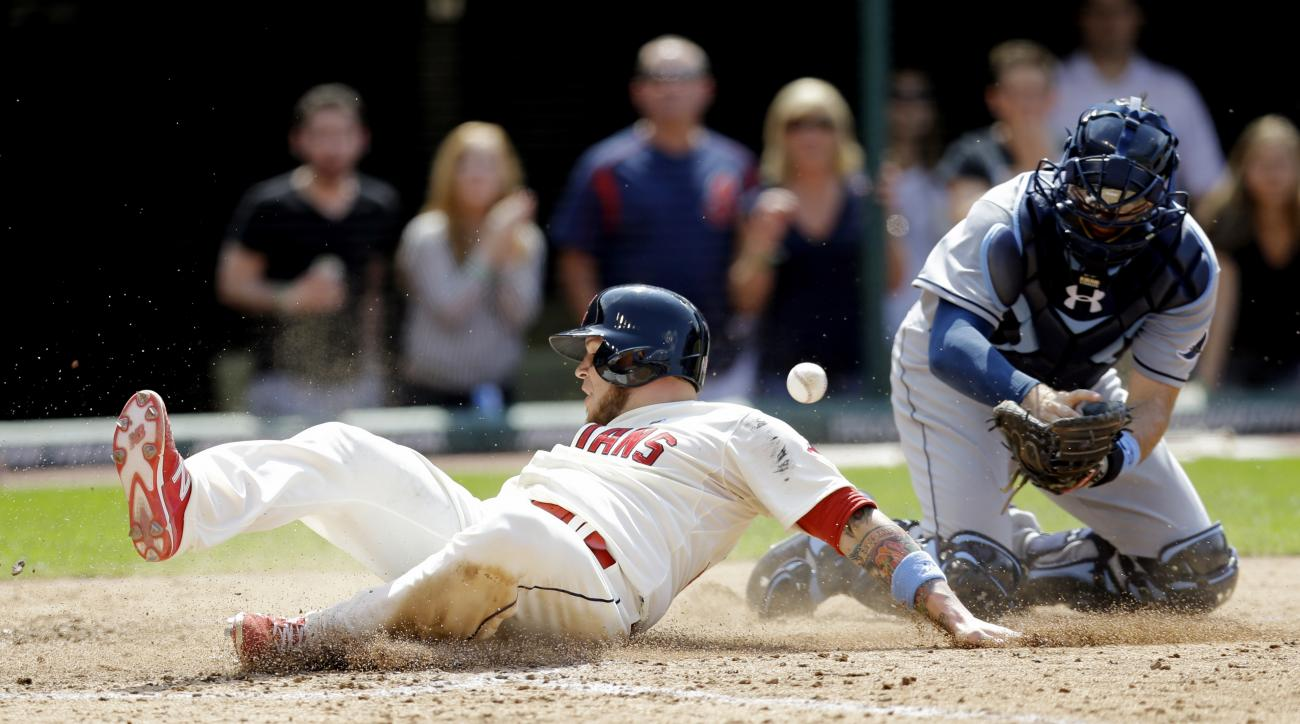 Cleveland Indians' Roberto Perez slides safely into home plate as Tampa Bay Rays' Curt Casali drops the ball in the ninth inning of a baseball game, Sunday, June 21, 2015, in Cleveland. Perez scored on a sacrifice fly by David Murphy. The Indians won 1-0.