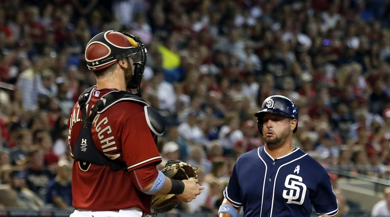 San Diego Padres Yonder Alonso, right, scores on a ball hit by Matt Kemp in the sixth inning during a baseball game against the Arizona Diamondbacks, Sunday, June 21, 2015, in Phoenix. (AP Photo/Rick Scuteri)