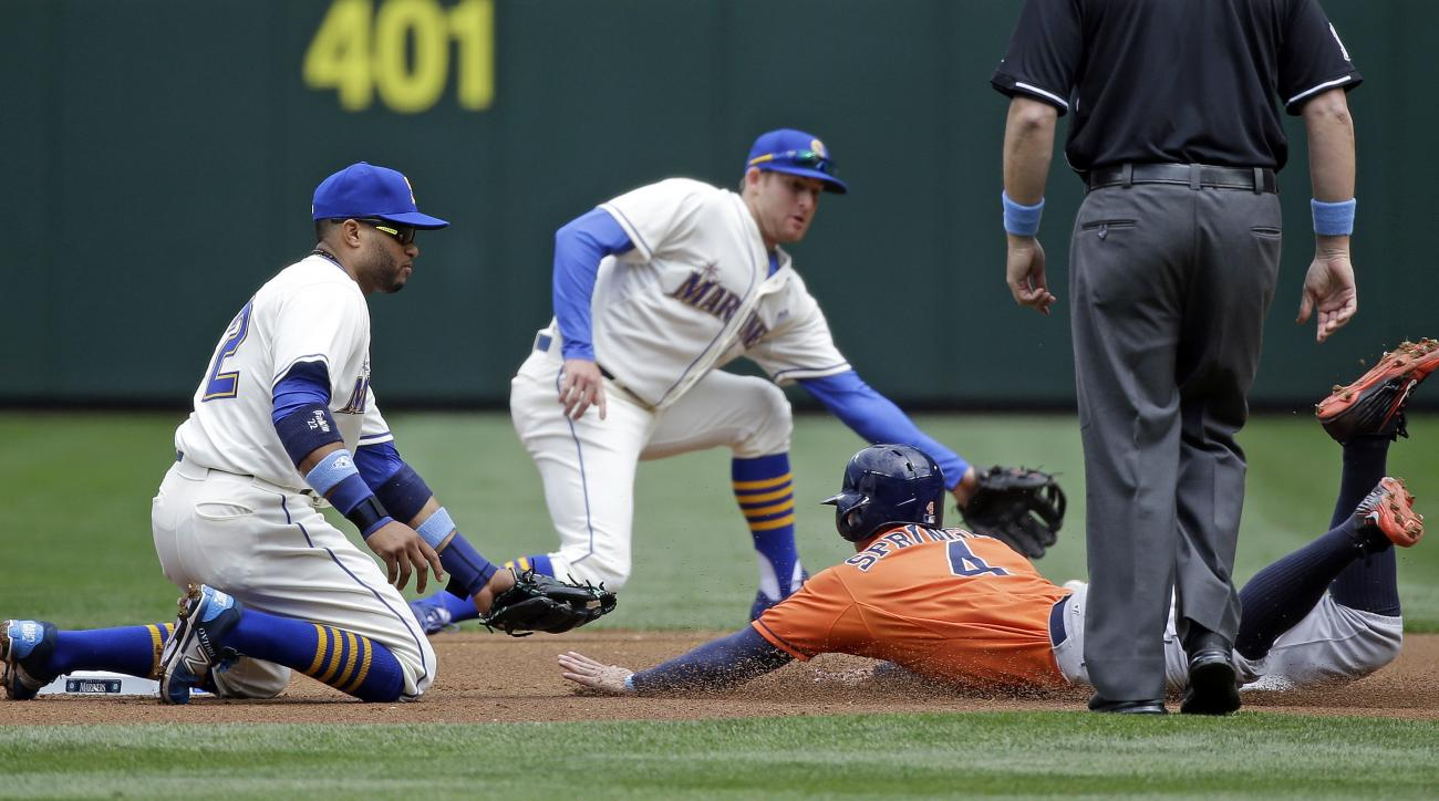 Houston Astros' George Springer (4) slides safely into second base as the ball gets past both Seattle Mariners second baseman Robinson Cano, left, and shortstop Brad Miller in the first inning of a baseball game Sunday, June 21, 2015, in Seattle. Springer