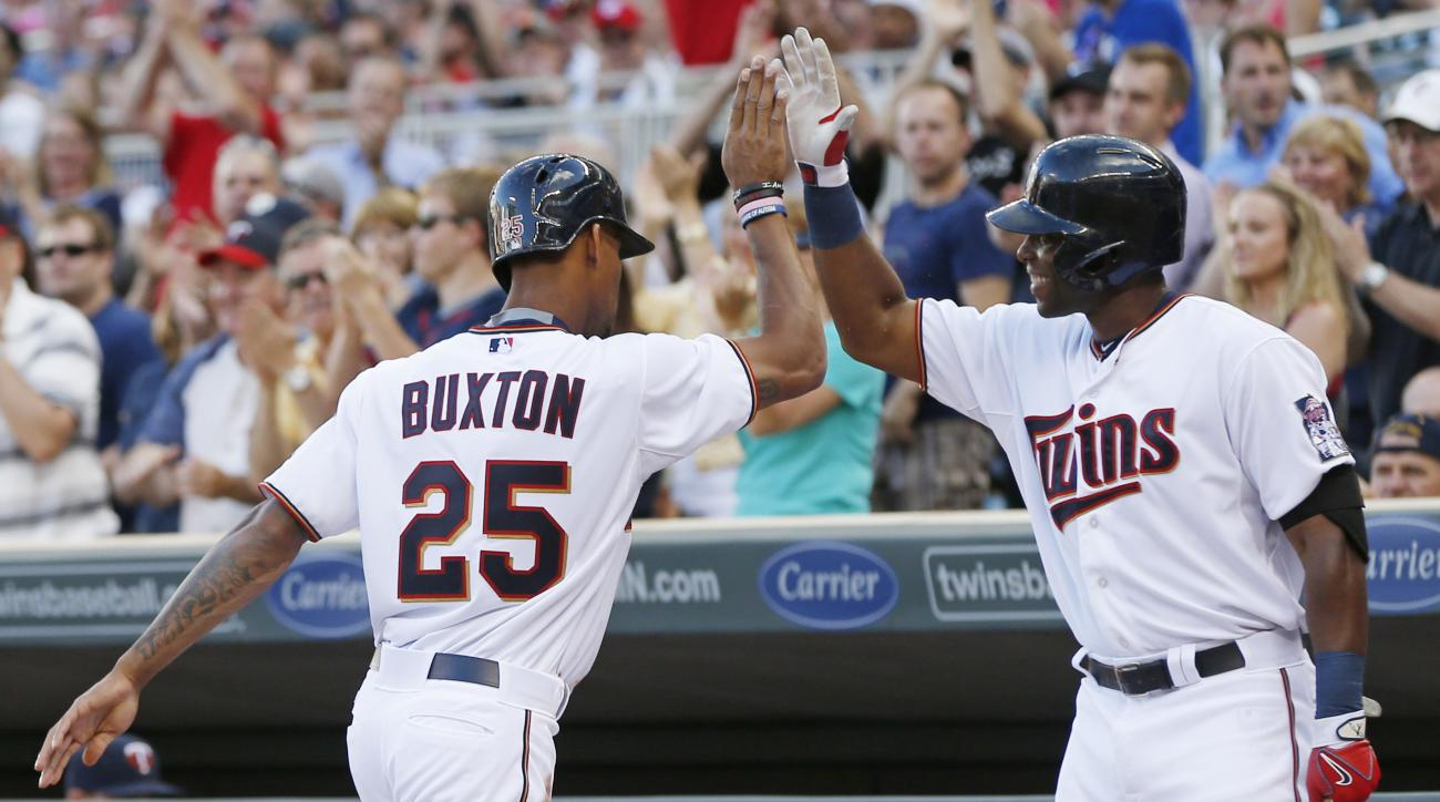 Minnesota Twins' Torii Hunter, right, congratulates Byron Buxton after he scored on a single by Brian Dozier in the first inning of a baseball game, Monday, June 22, 2015, in Minneapolis. (AP Photo/Jim Mone)