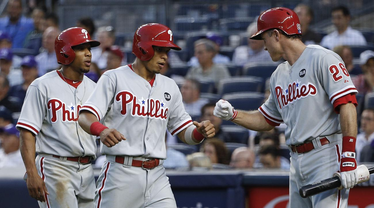 Philadelphia Phillies' Chase Utley (26) greets Cesar Hernandez, center, and Ben Revere after the two scored against the New York Yankees during the third inning of a baseball game, Monday, June 22, 2015, in New York. (AP Photo/Julie Jacobson)
