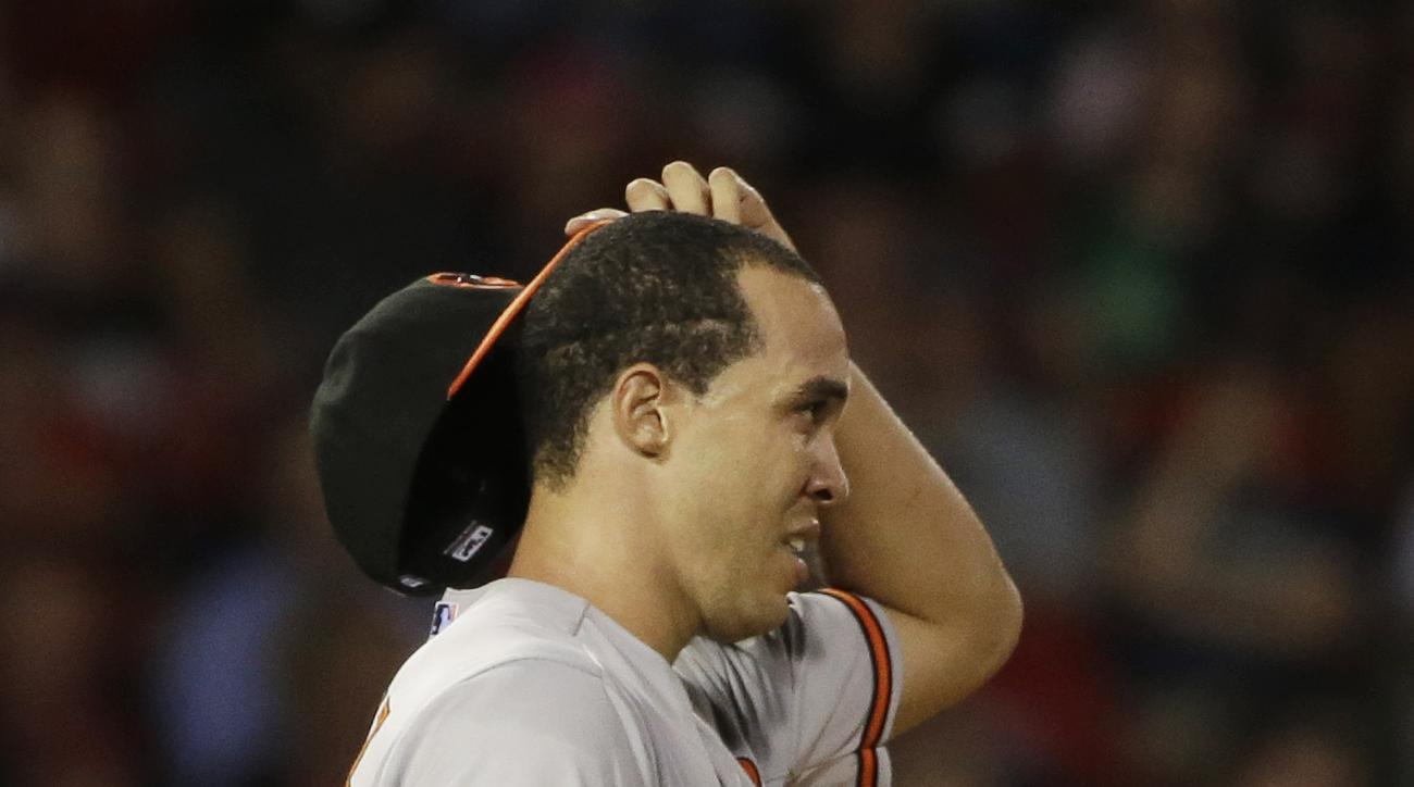 Baltimore Orioles' Ubaldo Jimenez removes his hat after giving up a hit to the Boston Red Sox in the fifth inning of a baseball game at Fenway Park, Tuesday, June 23, 2015, in Boston. (AP Photo/Steven Senne)
