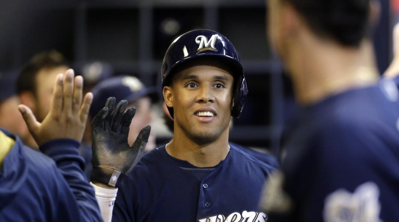 Milwaukee Brewers' Carlos Gomez is congratulated in the dugout after scoring on a hit by Adam Lind during the seventh inning of a baseball game against the New York Mets Tuesday, June 23, 2015, in Milwaukee. (AP Photo/Morry Gash)