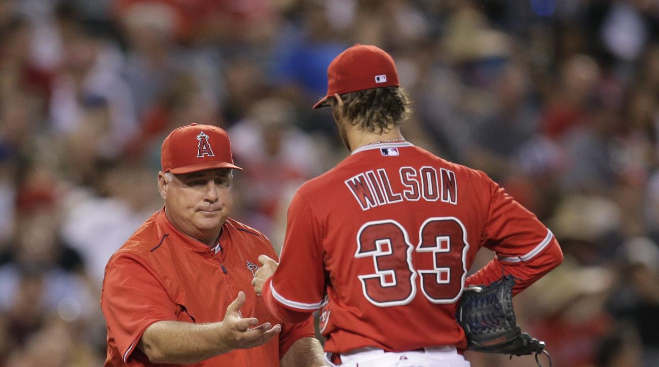 Los Angeles Angels starting pitcher C.J. Wilson, center, hands the ball to manager Mike Scioscia as he is relieved during the fourth inning of a baseball game against the Houston Astros, Tuesday, June 23, 2015, in Anaheim, Calif. (AP Photo/Jae C. Hong)