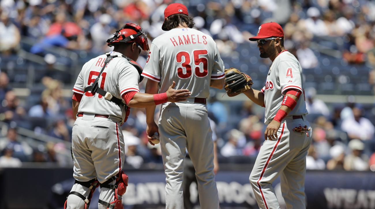 Philadelphia Phillies catcher Carlos Ruiz (51), and third baseman Andres Blanco (4) console starting pitcher Cole Hamels (35) in the second inning of a baseball game against the New York Yankees at Yankee Stadium in New York, Wednesday, June 24, 2015.  (A