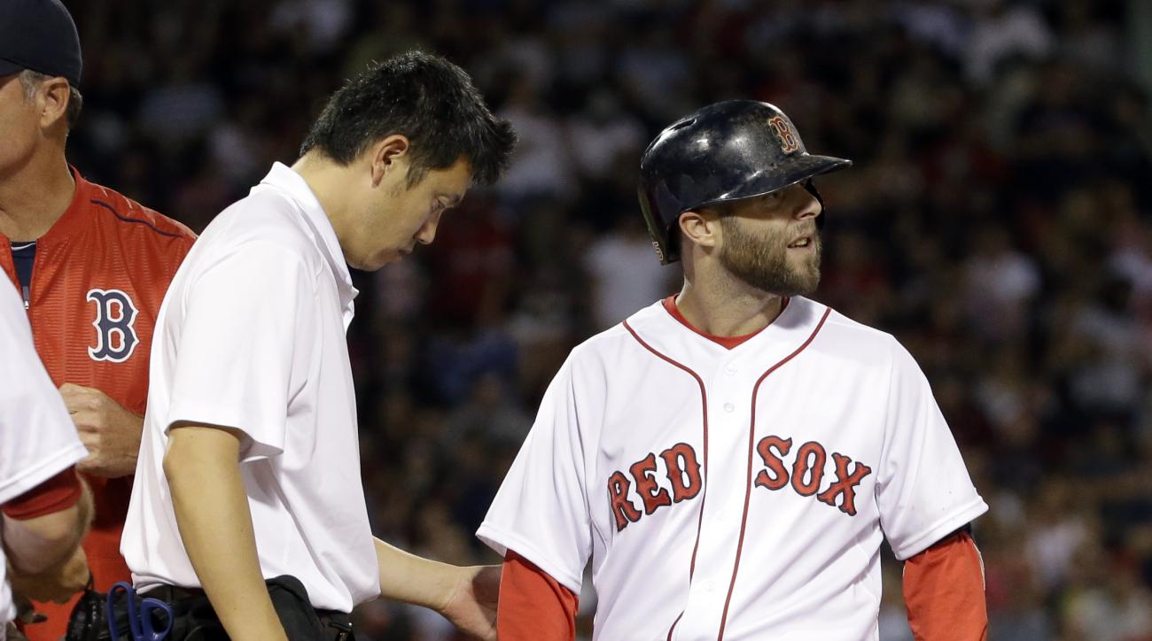 Boston Red Sox's Dustin Pedroia is checked by team trainer Masai Takahashi after injuring his leg rounding first base on a single during the sixth inning of a baseball game against the Baltimore Orioles at Fenway Park, Wednesday, June 24, 2015, in Boston.
