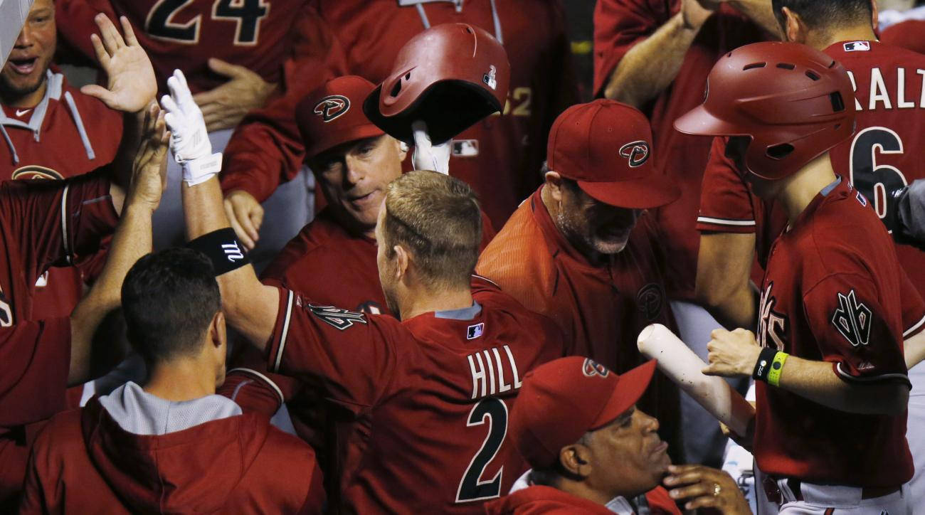 Arizona Diamondbacks third baseman Aaron Hill, center, is congratulated by teammates after hitting a sacrifice fly to bring in the go-ahead run off Colorado Rockies relief pitcher John Axford in the ninth inning of a baseball game Wednesday, June 24, 2015