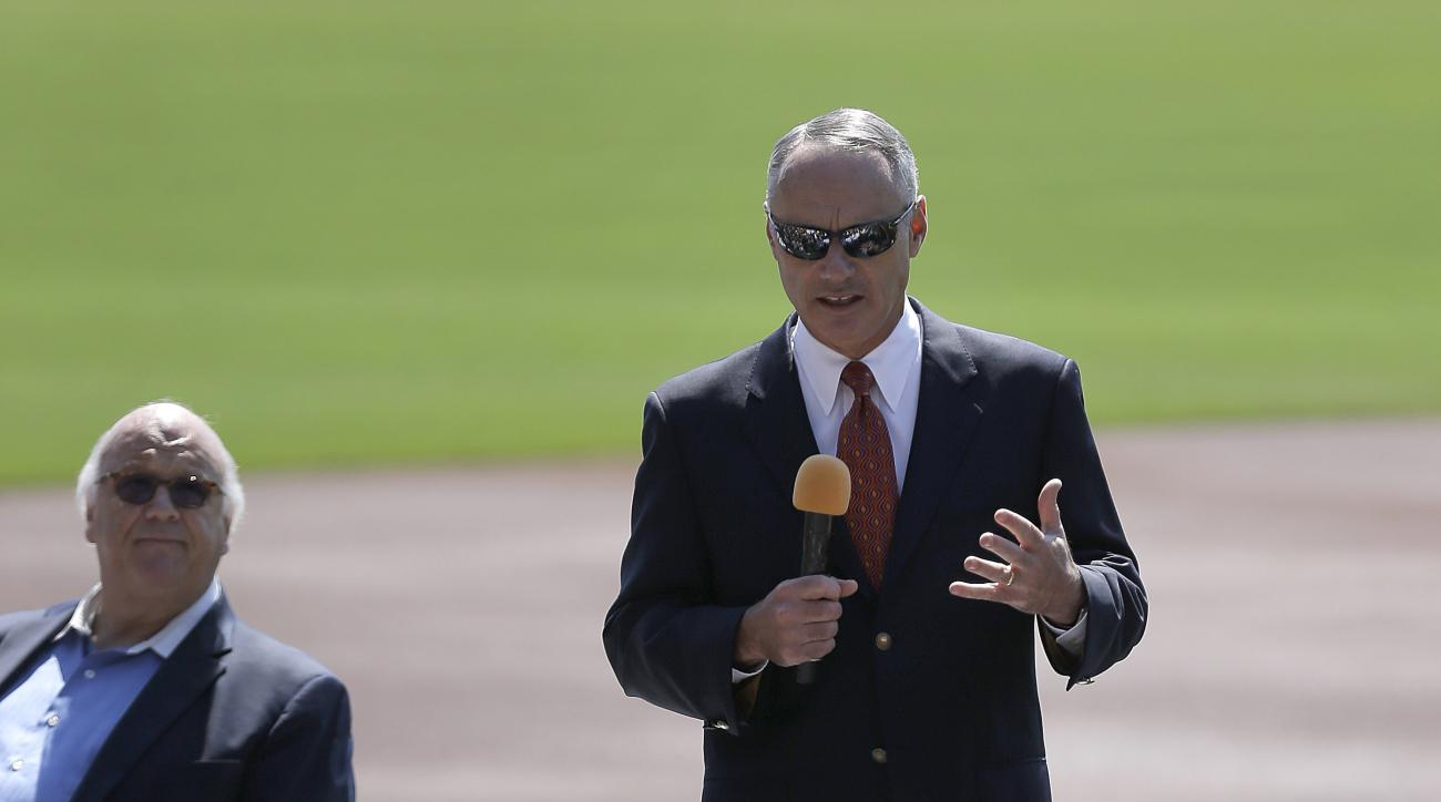 Baseball Commissioner Rob Manfred, right, gestures to AT & T Park employees beside Giants radio broadcaster Jon Miller, Thursday, June 25, 2015, prior to a baseball game between the San Diego Padres and the San Francisco Giants in San Francisco. (AP Photo