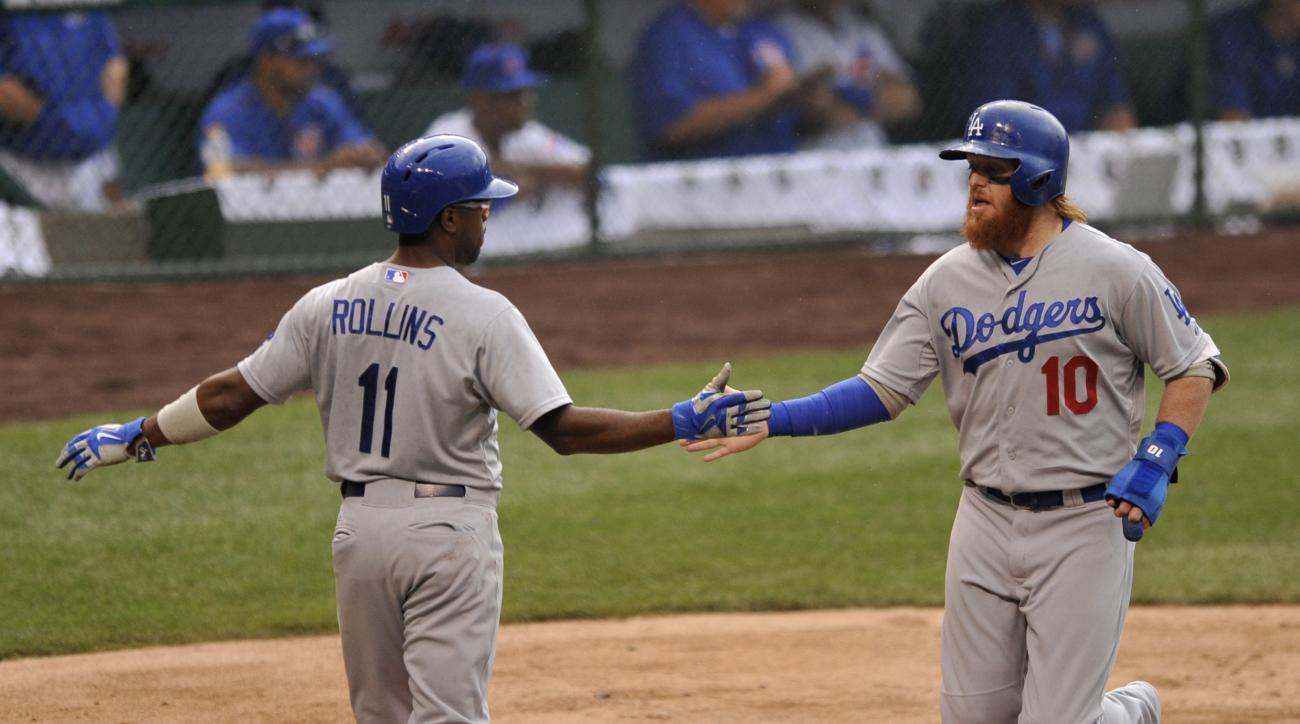 Los Angeles Dodgers' Justin Turner (10), celebrates with teammate Jimmy Rollins (11), after both scoring on a Howie Kendrick two-RBI double during the first inning of a baseball game against the Chicago Cubs, Thursday, June 25, 2015, in Chicago. (AP Photo