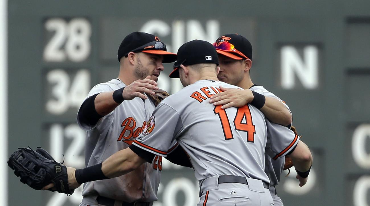 From left, Baltimore Orioles outfielders Steve Pearce, Nolan Reimold (14) and David Lough celebrate their 8-6 victory over the Boston Red Sox after a baseball game at Fenway Park, Thursday, June 25, 2015, in Boston. (AP Photo/Elise Amendola)