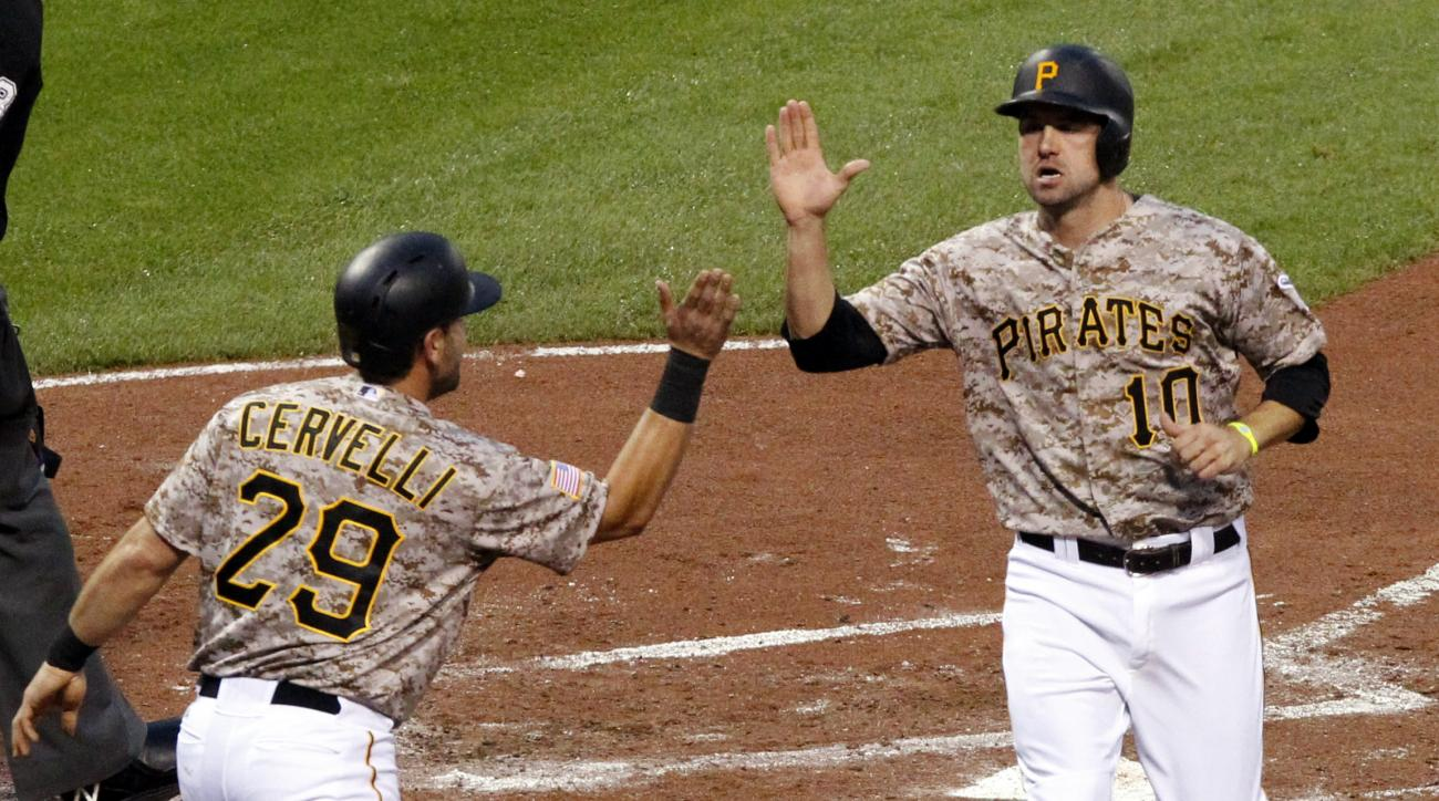 Pittsburgh Pirates' Jordy Mercer (10) celebrates with teammate Francisco Cervelli (29) after both scored on a single by starting pitcher A.J. Burnett off Cincinnati Reds starting pitcher Anthony DeSclafani during the second inning of a baseball game in Pi