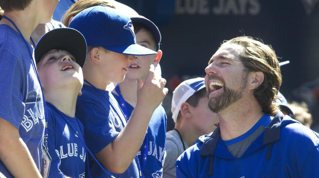 Toronto Blue Jays pitcher R.A Dickey talks to young Jays fans from Nashville, Tenn., at batting practice for the team's baseball game against the Texas Rangers in Toronto on Friday, June 26, 2015. (Fred Thornhill/The Canadian Press via AP)