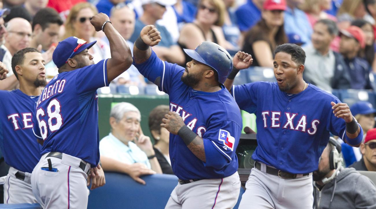 Texas Rangers' Prince Fielder, center, is congratulated by teammates after he hit a home run against the Toronto Blue Jays in the first inning of a baseball game in Toronto, Friday, June 26, 2015. (Fred Thornhill/The Canadian Press via AP) MANDATORY CREDI