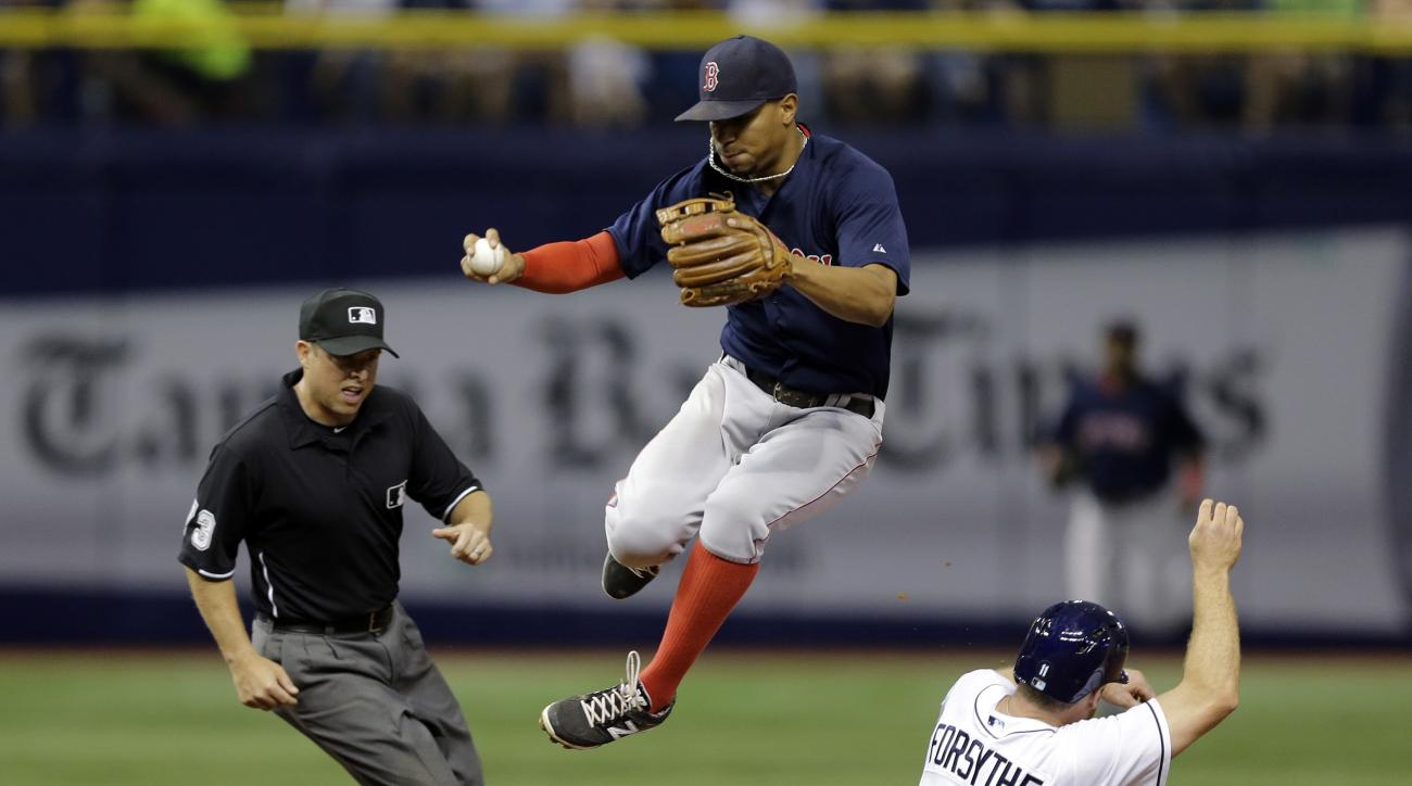 Boston Red Sox shortstop Xander Bogaerts, center, leaps over Tampa Bay Rays' Logan Forsythe (11) after forcing him at second base on a fielder's choice by Rays' Steven Souza Jr. during the sixth inning of a baseball game Friday, June 26, 2015, in St. Pete