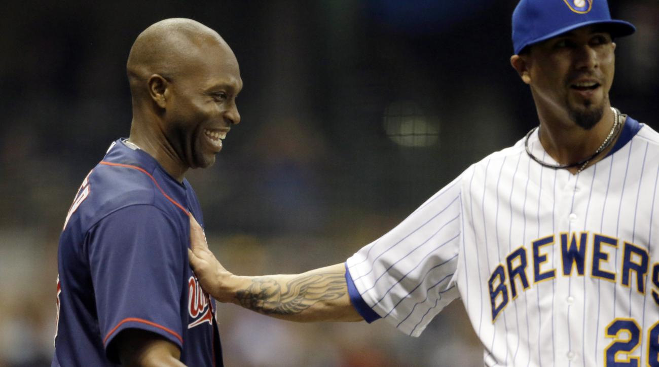 Milwaukee Brewers starting pitcher Kyle Lohse, right, pats Minnesota Twins' Torii Hunter on the chest after Hunter lined out to Brewers' Scooter Gennett during the fifth inning of a baseball game Friday, June 26, 2015, in Milwaukee. (AP Photo/Jeffrey Phel