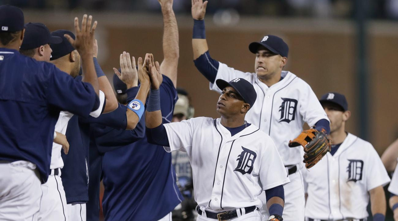 Detroit Tigers' Yoenis Cespedes, center, and teammates celebrate their 5-4 win over the Chicago White Sox in a baseball game, Friday, June 26, 2015, in Detroit. (AP Photo/Carlos Osorio)