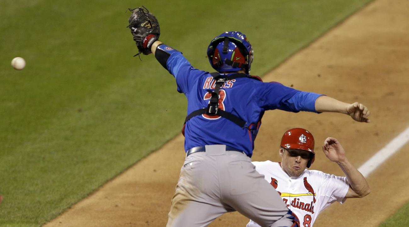 St. Louis Cardinals' Peter Bourjos, bottom, scores the game-winning run as the throw gets past Chicago Cubs catcher David Ross during the 10th inning of a baseball game Friday, June 26, 2015, in St. Louis. The Cardinals won 3-2. (AP Photo/Jeff Roberson)