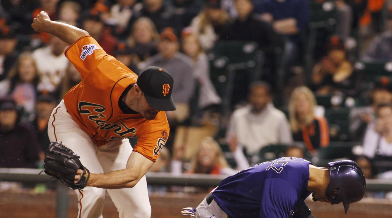 Colorado Rockies' Carlos Gonzalez (5) slides safely home under the tag by San Francisco Giants pitcher Mike Broadway during the ninth inning of a baseball game, Friday, June 26, 2015, in San Francisco. Gonzalez scored on a wild pitch. (AP Photo/George Nik