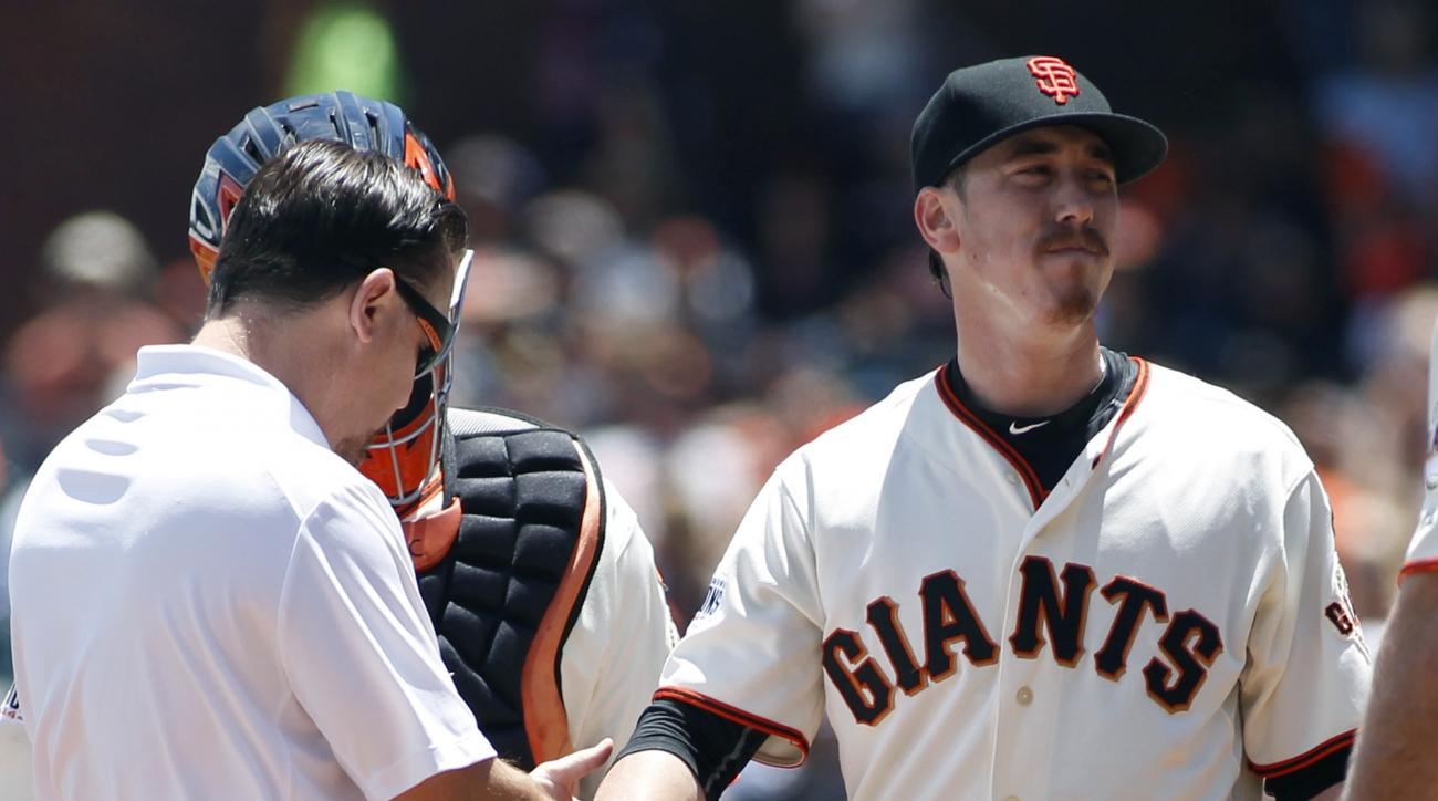 San Francisco Giants trainer Dave Groeschner, left, checks Tim Lincecum's right wrist during the second inning of a baseball game against the Colorado Rockies, Saturday, June 27, 2015, in San Francisco. (AP Photo/George Nikitin)