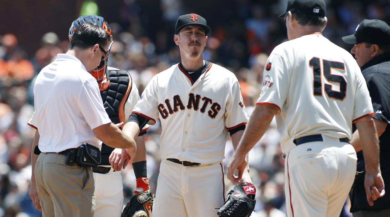San Francisco Giants trainer Dave Groeschner, left, checks Tim Lincecum's right wrist during the second inning of a baseball game against the Colorado Rockies, Saturday, June 27, 2015, in San Francisco. Giants manager, Bruce Bochy (15) is at right. (AP Ph