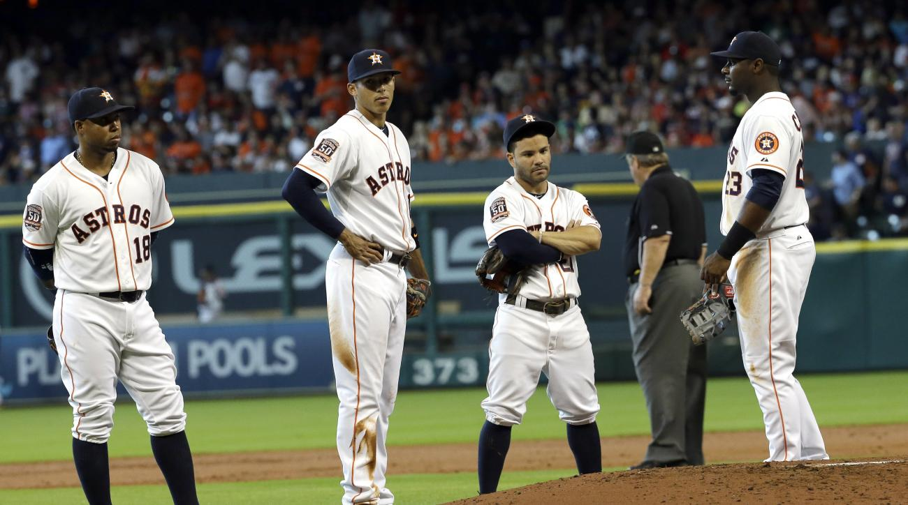 Houston Astros Luis Valbuena (18), Carlos Correa (1), Jose Altuve and Chris Carter (23) wait for new pitcher after starter Brett Oberholtzer was ejected from the game by home plate umpire Rob Drake during the second inning of a baseball game against the N