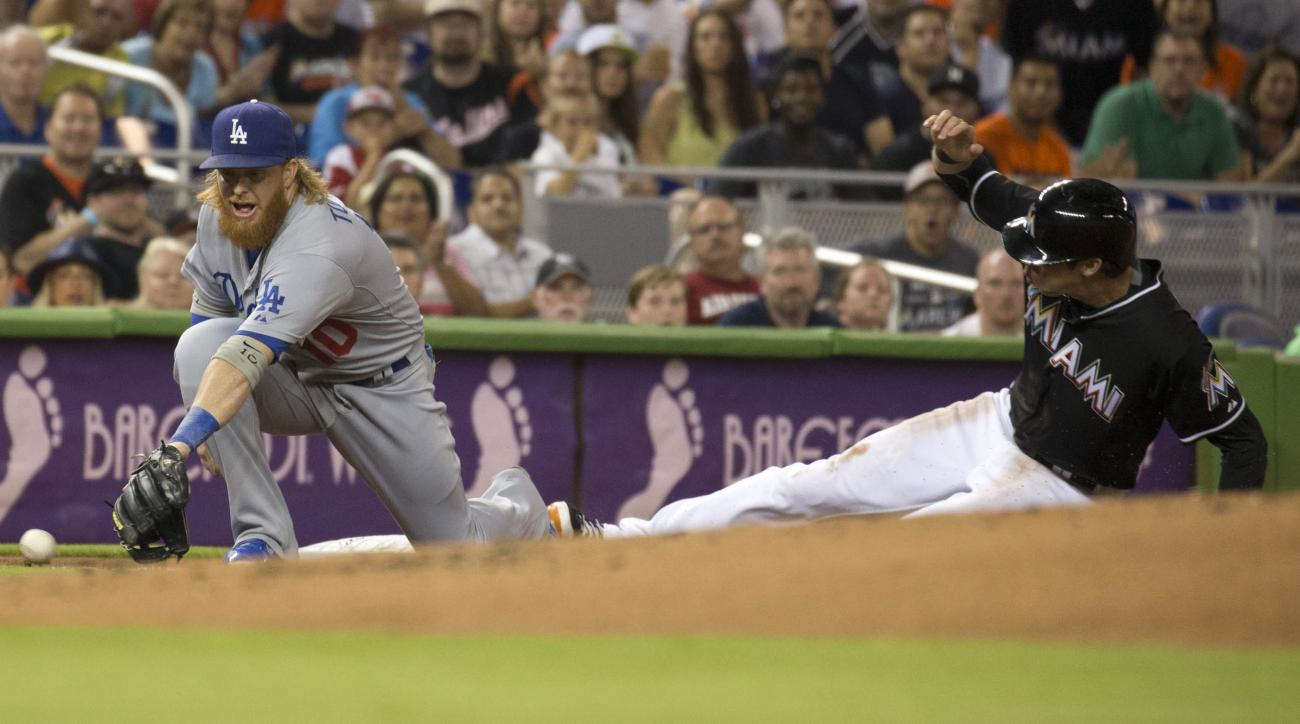 Los Angeles Dodgers third baseman Justin Turner (10) misses the ball as Miami Marlins' Christian Yelich (21) slides into third during the first inning of a baseball game in Miami, Saturday, June 27, 2015. (AP Photo/J Pat Carter)