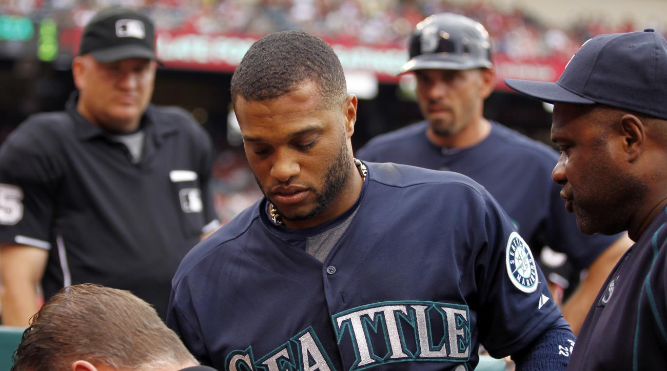 Seattle Mariners' Robinson Cano, center, is taken from the bench by trainer Rob Nodine, and manager Lloyd McClendon, right, with a knot on his forehead, after an overthrow by the Los Angeles Angels throwing infield warmups to begin the seventh inning hit