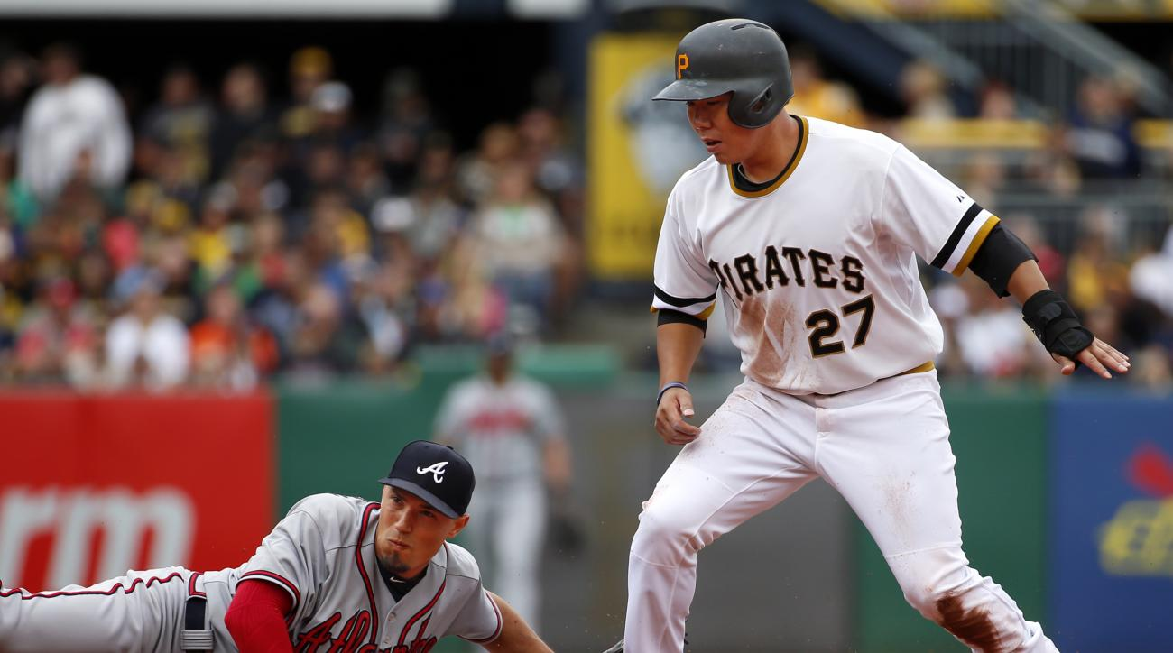 Pittsburgh Pirates' Jung Ho Kang (27) steals second ahead of the tag by Atlanta Braves shortstop Andrelton Simmons in the first inning of a baseball game in Pittsburgh, Sunday, June 28, 2015. (AP Photo/Gene J. Puskar)