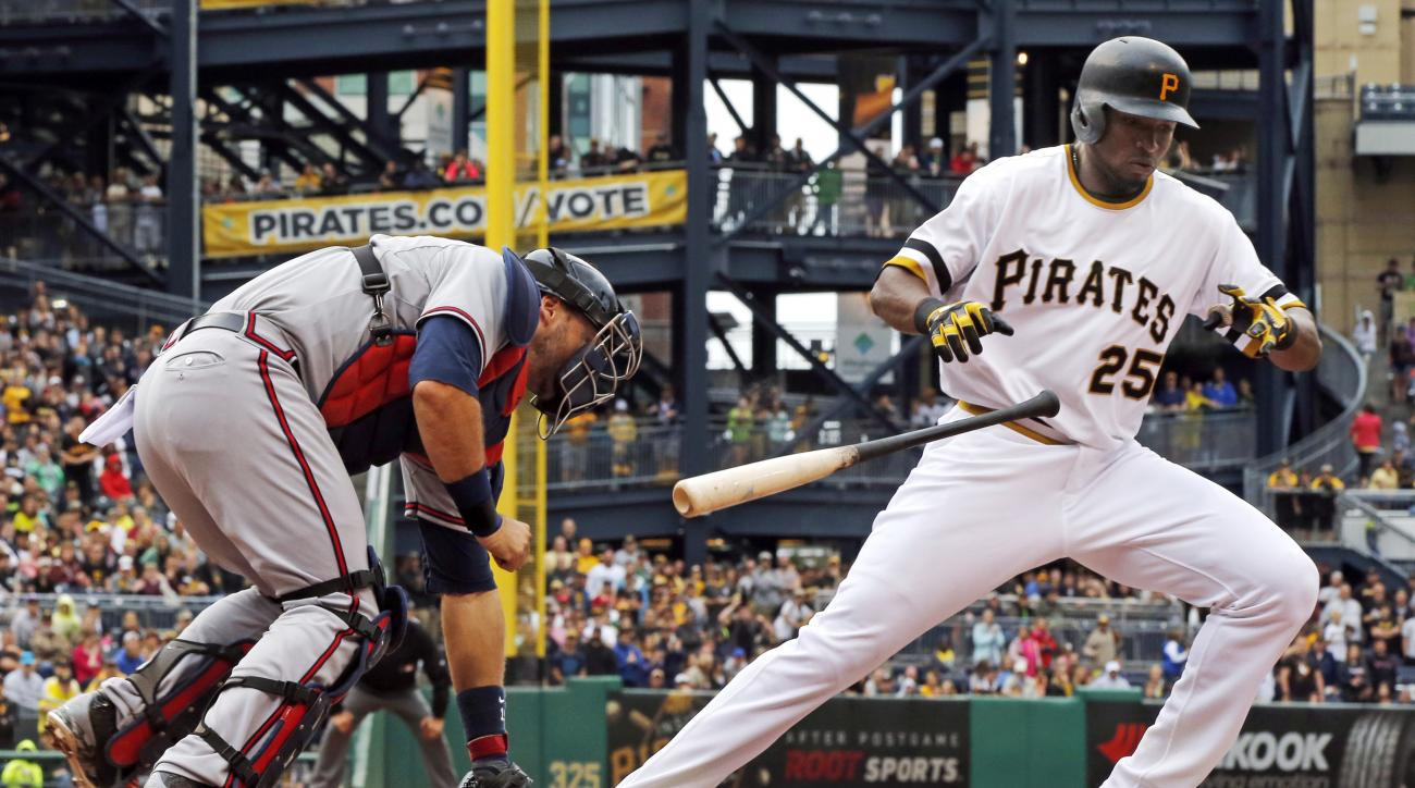 Atlanta Braves catcher A.J. Pierzynski, left, picks up the ball in front of the plate as Pittsburgh Pirates' Gregory Polanco (25) breaks for first base in the ninth inning of a baseball game in Pittsburgh, Sunday, June 28, 2015. Pierzynski threw to first