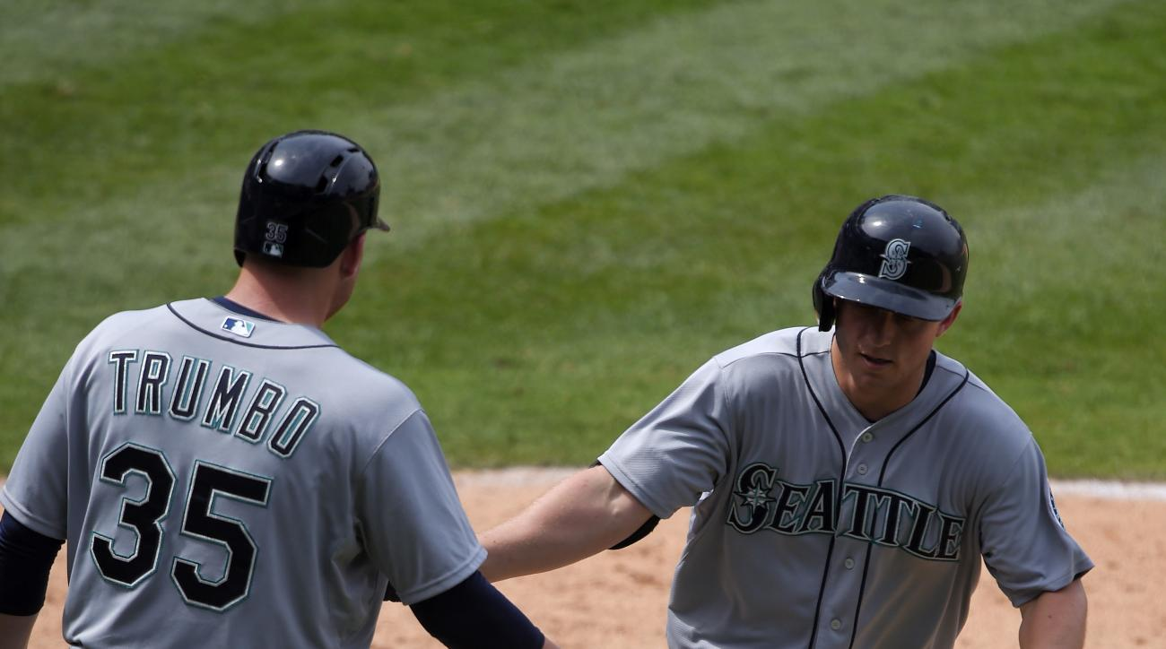 Seattle Mariners' Kyle Seager, right, is congratulated by Mark Trumbo after hitting a solo home run during the ninth inning of a baseball game against the Los Angeles Angels, Sunday, June 28, 2015, in Anaheim, Calif. (AP Photo/Mark J. Terrill)