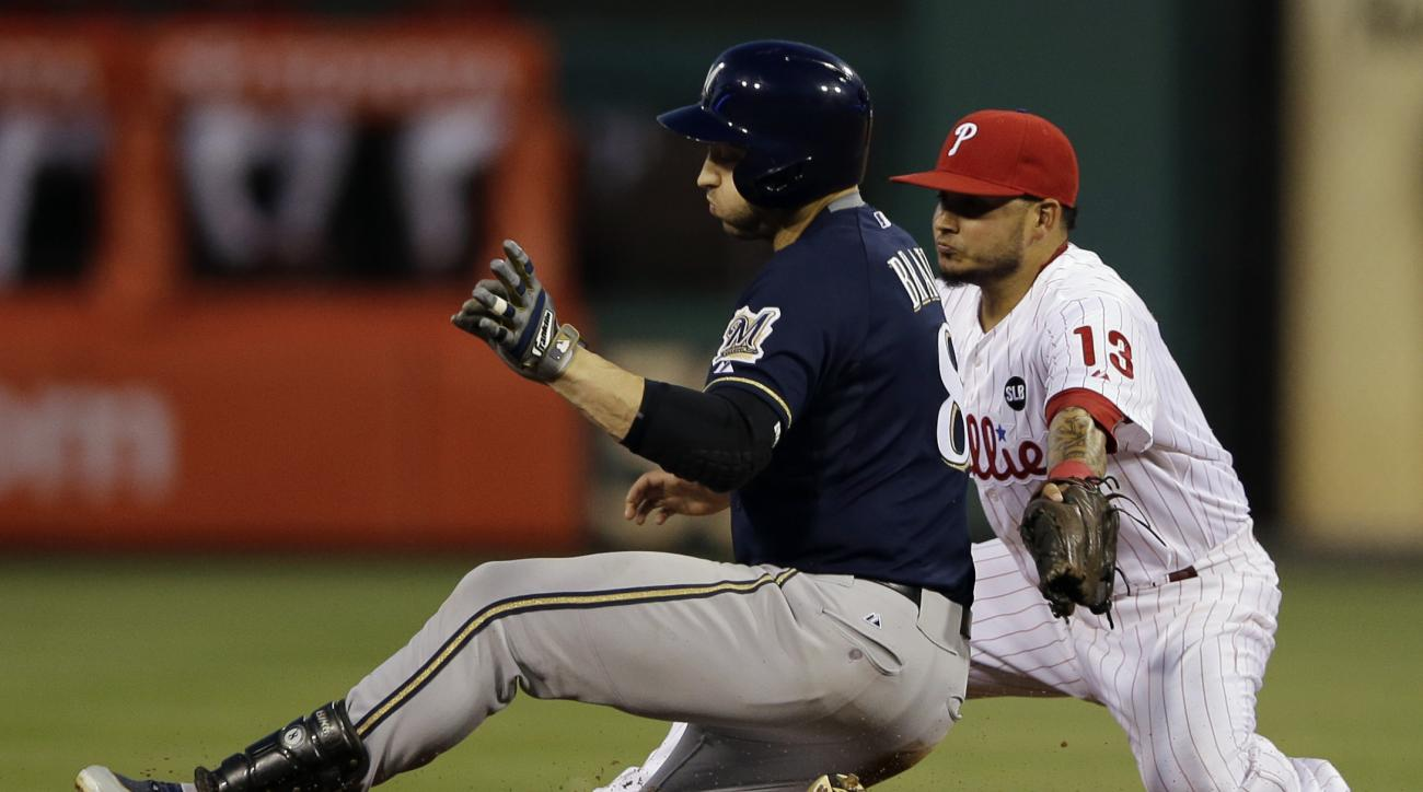 Milwaukee Brewers' Ryan Braun, left, slides into second base for an RBI-double past Philadelphia Phillies shortstop Freddy Galvis during the fifth inning of a baseball game, Monday, June 29, 2015, in Philadelphia. Milwaukee won 7-4. (AP Photo/Matt Slocum)