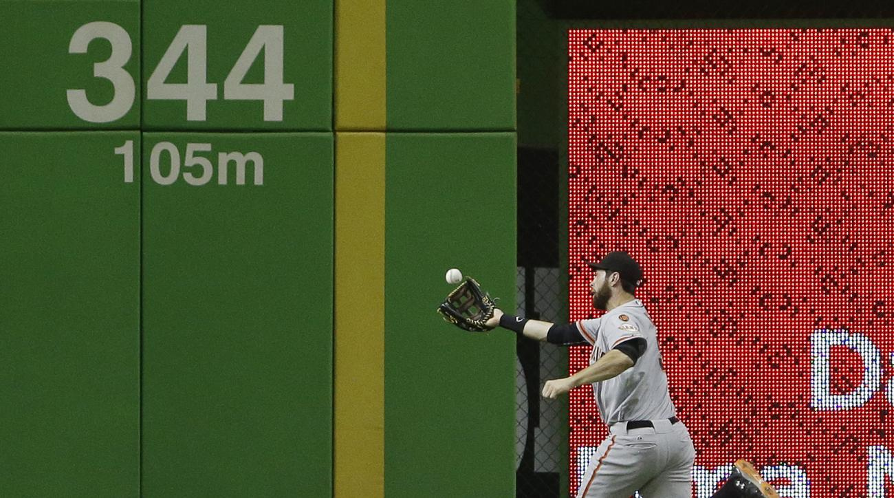 San Francisco Giants left fielder Brandon Belt catches a ball hit by Miami Marlins' Derek Dietrich during the fifth inning of a baseball game, Tuesday, June 30, 2015, in Miami. (AP Photo/Wilfredo Lee)