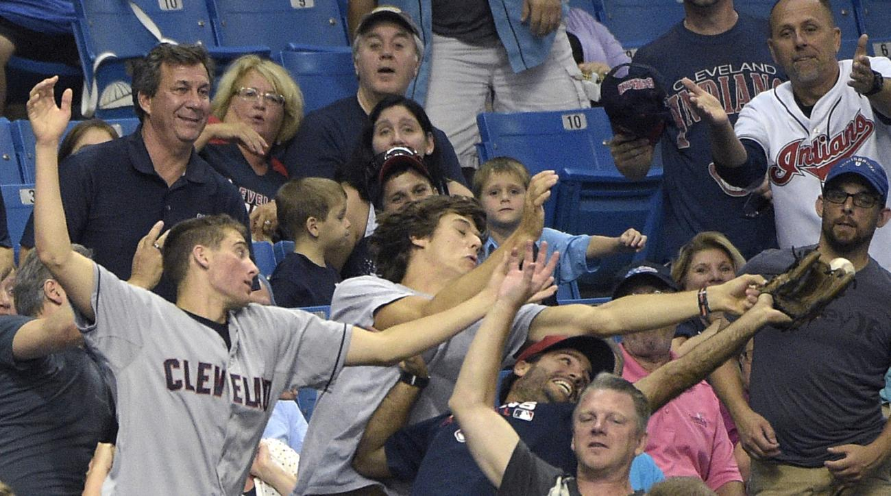 Fans attempt to catch a foul ball hit into the stands by Cleveland Indians' Michael Brantley during the eighth inning of a baseball game against the Tampa Bay Rays in St. Petersburg, Fla., Tuesday, June 30, 2015. (AP Photo/Phelan M. Ebenhack)