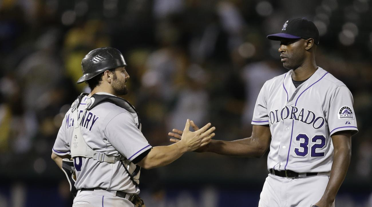 Colorado Rockies' LaTroy Hawkins, right, and Michael McKenry celebrate the team's 2-1 defeat of the Oakland Athletics in a baseball game Tuesday, June 30, 2015, in Oakland, Calif. (AP Photo/Ben Margot)