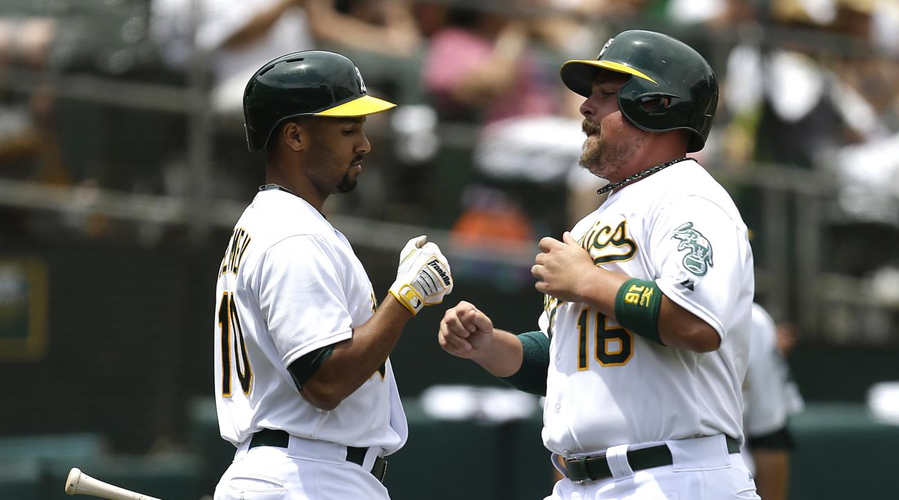 Oakland Athletics' Billy Butler, right, is congratulated by Marcus Semien (10) after Butler scored against the Colorado Rockies in the second inning of a baseball game Wednesday, July 1, 2015, in Oakland, Calif. Butler scored on a sacrifice fly by A's Eri