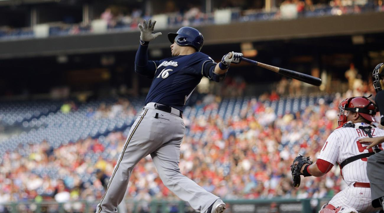 Milwaukee Brewers' Aramis Ramirez, left, follows through after hitting a two-run double off Philadelphia Phillies starting pitcher Aaron Harang as catcher Carlos Ruiz, right, watches during the third inning of a baseball game, Wednesday, July 1, 2015, in