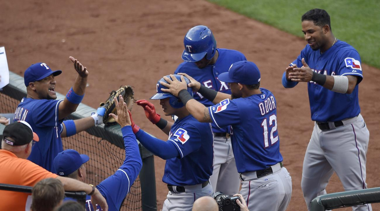 Texas Rangers' Shin-Soo Choo, of South Korea, center, is mobbed by teammates including Rougned Odor (12) after he hit a home run against the Baltimore Orioles during the third inning of a baseball game, Wednesday, July 1, 2015, in Baltimore. (AP Photo/Nic